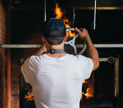Баркли mans the wood-fired Grillworks grill